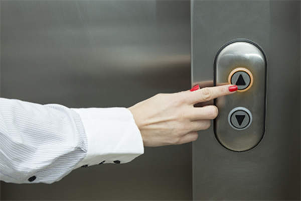 Woman pushing button on work place elevator.