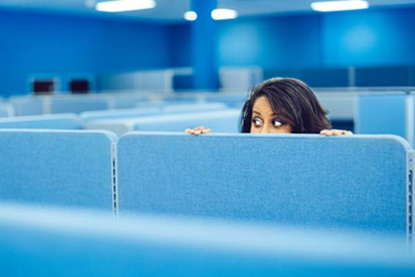 Scared woman hiding in an office cubicle.