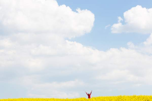 "Distant woman in wildflower field, arms raised in a ""v"", enjoying freedom."