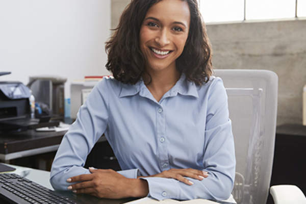 Smiling woman at work wearing light dress shirt at desk.