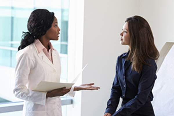 Female doctor talking to young woman image.