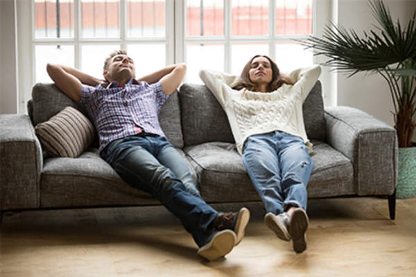 Couple relaxing on couch at home.