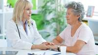 Senior woman discussing uterine cancer prognosis with her doctor.