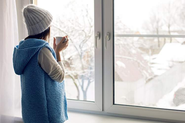 Woman looking out her window at the snow outside.