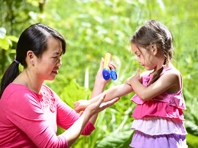 Woman putting sunscreen on young girl.