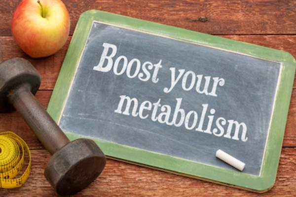 Boost your metabolism written on small chalkboard, with apple, weight, and measuring tape along side.