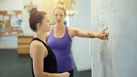 A woman and her trainer looking at an exercise plan on a white board.