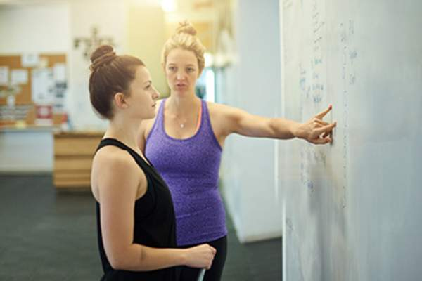 Woman working with trainer to develop an exercise program.