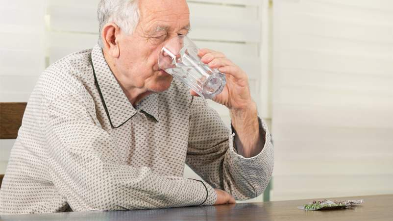 Senior man taking medication with glass of water.