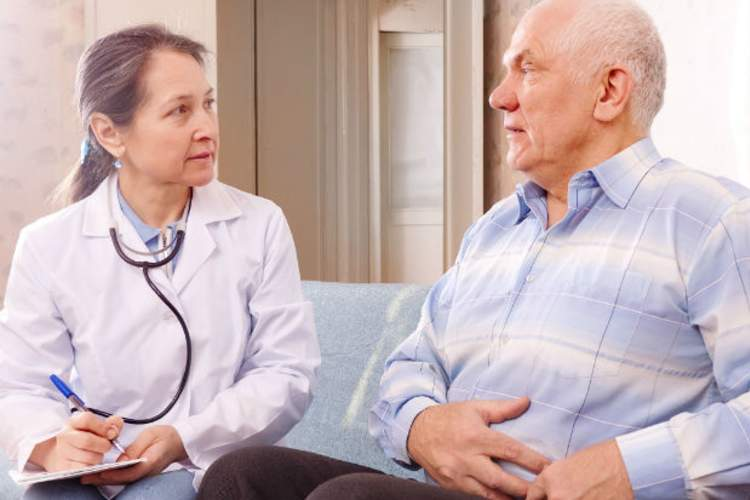 man talking with doctor about stomach issues
