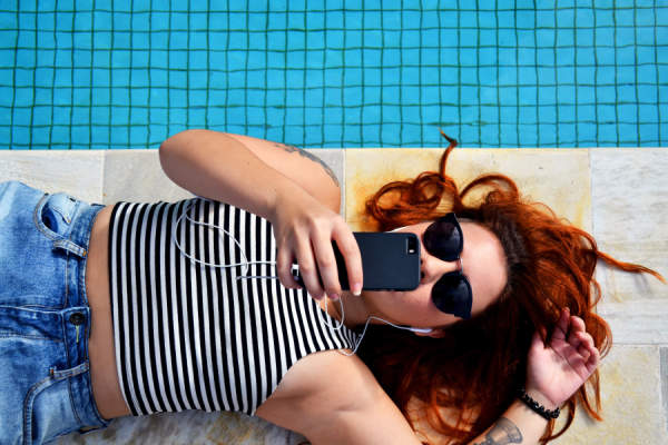 woman next to pool taking selfie