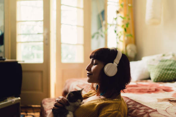 girl holding cat relaxing with headphones