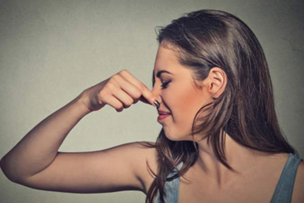 Woman pinches nose with fingers looks with disgust