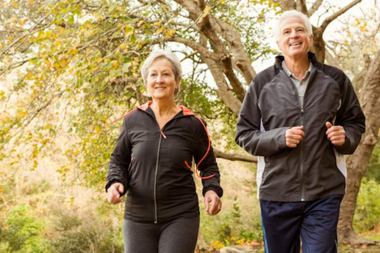 Happy retired couple jogging in park, depression isn't normal aging.