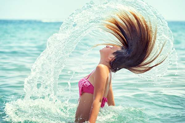 Girl flipping her hair out of the ocean.