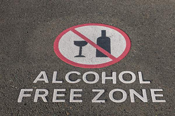 Alcohol free zone sign on pavement.