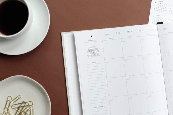 calendar on table with paper clips and coffee