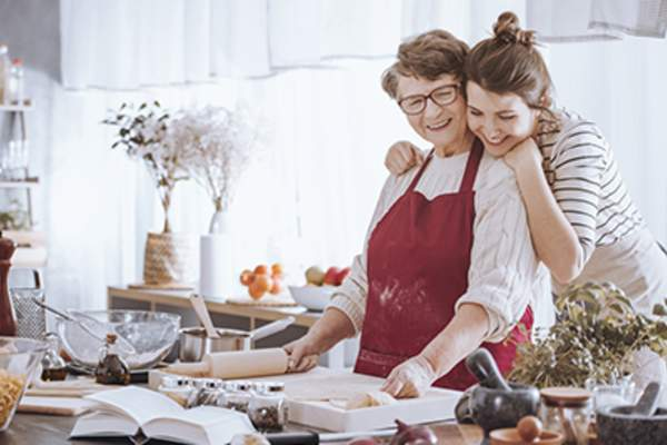 Woman hugging her mother in the kitchen.