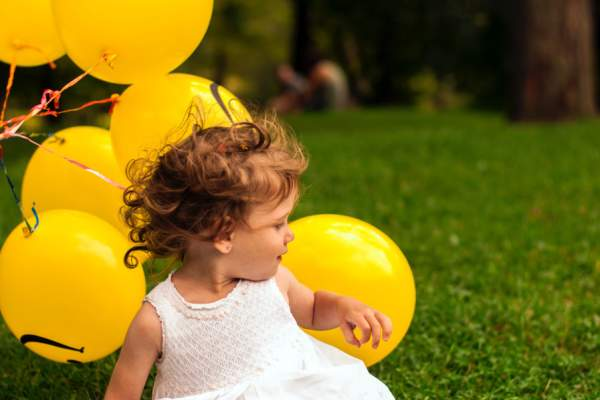 toddler with smiley face balloons