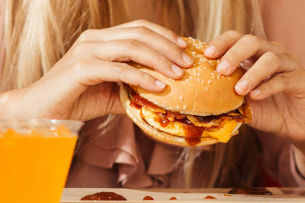 woman's hands eating burger