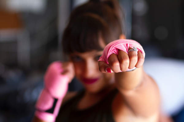 woman with pink tape of hands in boxing stance