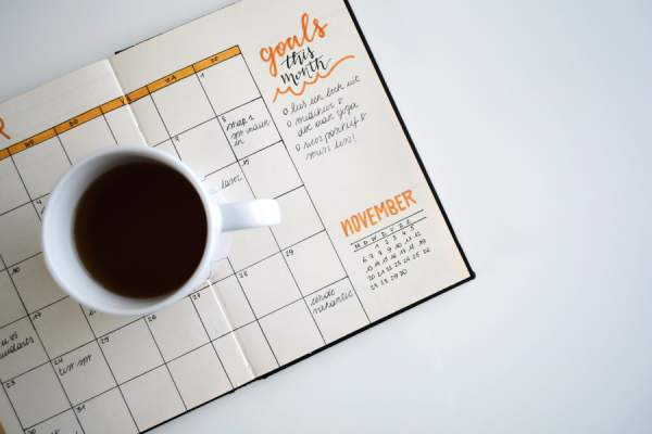 "coffee mug sitting on top of day planner reading ""goals for this month"""