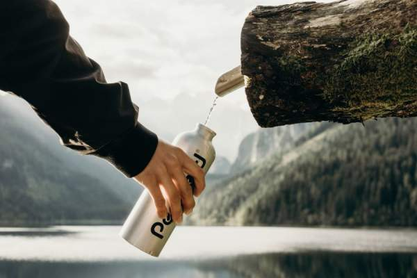 man refilling water bottle in nature