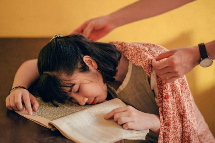 疲惫的年轻女子读着书睡着了。