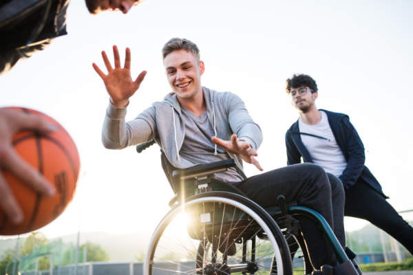 young man in wheelchair playing basketball