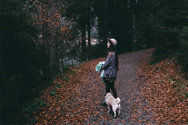 Woman and her dog taking a walk on a wooded path.