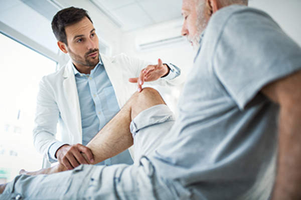 Doctor examining a patient's knee pain.