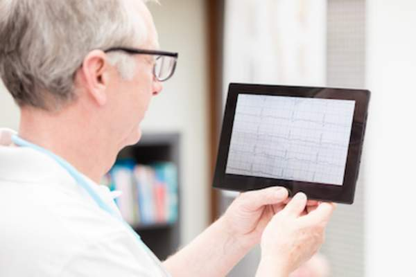 Doctor reviewing event monitor read out on tablet