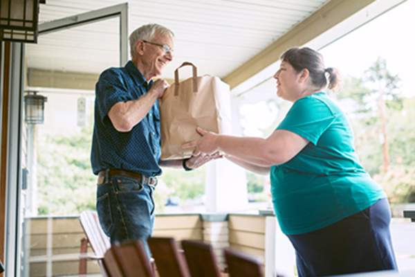Woman delivering groceries to a senior man.