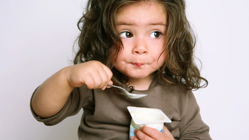 Little girl eating yogurt with a spoon.
