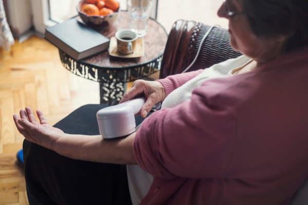 Senior woman using hand massager at home