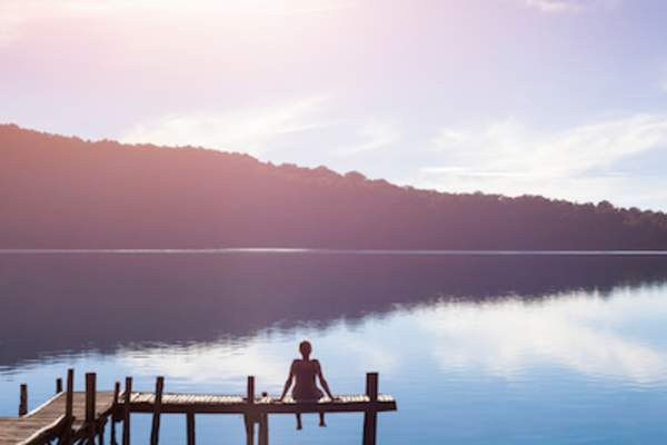 Woman sitting on pier looking out over lake.