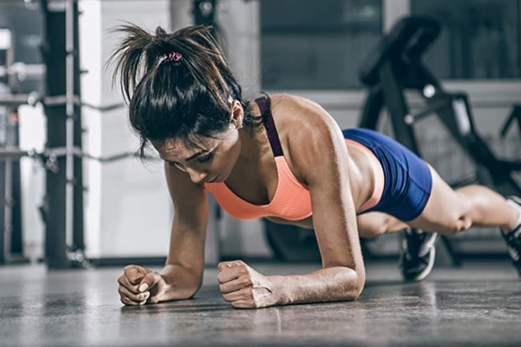 Muscular woman in a plank position