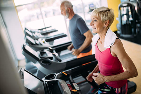 Middle age man and woman at the gym running on treadmills.
