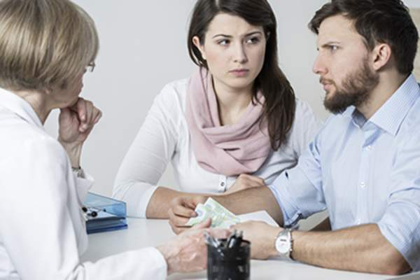 Couple talking to doctor about fertility issues.
