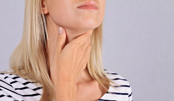 Woman feeling her thyroid glands