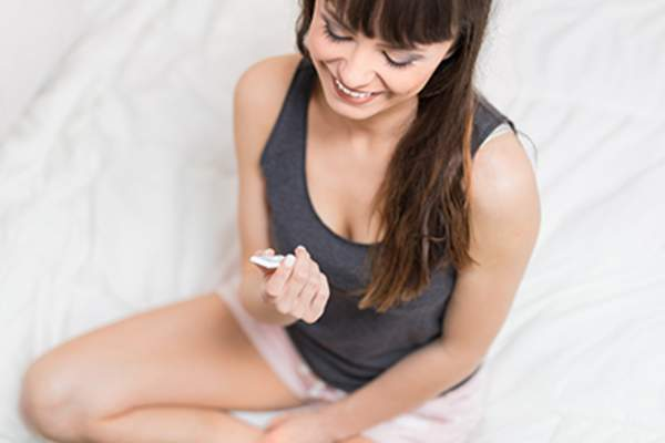 Happy young woman with pregnancy test sitting on bed.