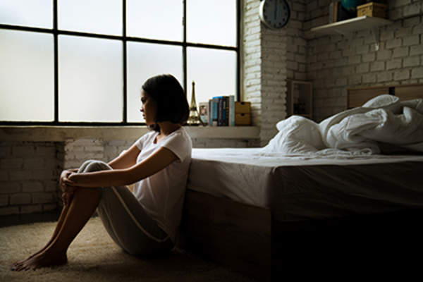 Sad woman sitting at the foot of her bed.