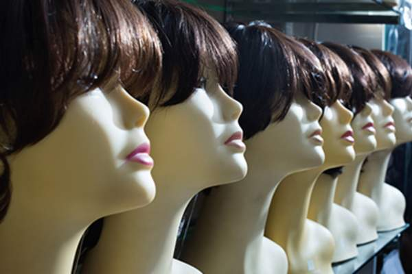 Mannequins with brunet style wigs on shelves