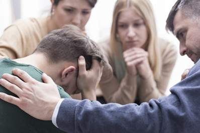 Support group comforting man.