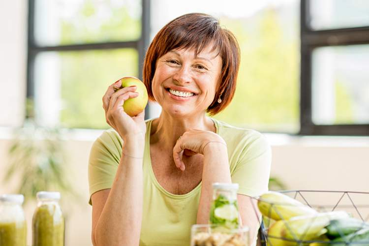 Healthy woman holding an apple.