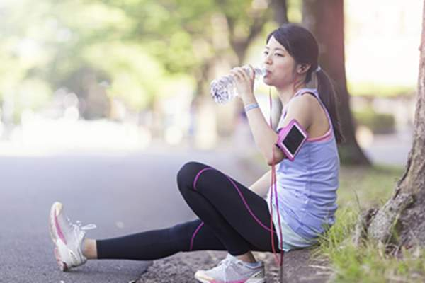 Woman resting during a run and drinking water.