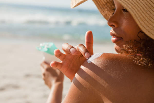 woman in sunhat putting on sunscreen