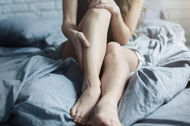 Woman holding her leg in bed.