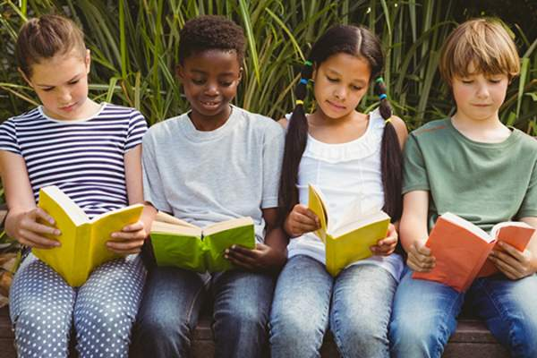 Kids reading books outside in the park in the summer.