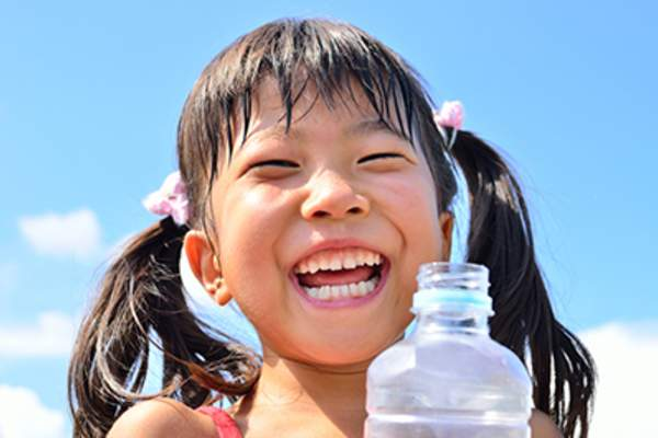Laughing young girl with water bottle.
